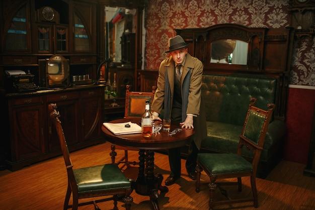 Detective masculino con sombrero y abrigo en la escena del crimen, estilo retro. investigación criminal, pruebas de búsqueda del inspector, interior de la habitación vintage