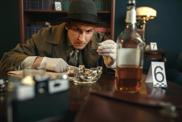 Detective con pinzas encuentra evidencia,
