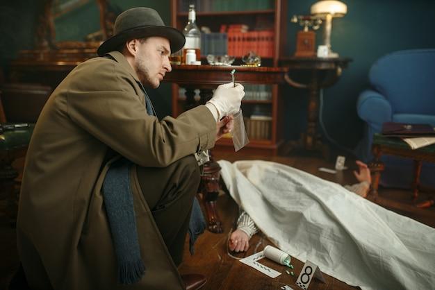 Detective con pinzas toma evidencia en la escena del crimen