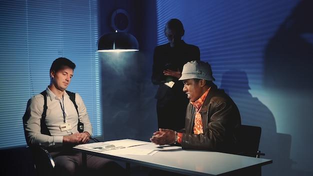 El detective de la policía le da a un criminal negro un documento para firmar.