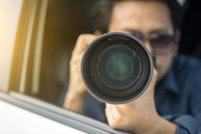 Detective privado que se sienta dentro de la cámara del coche con la cámara slr