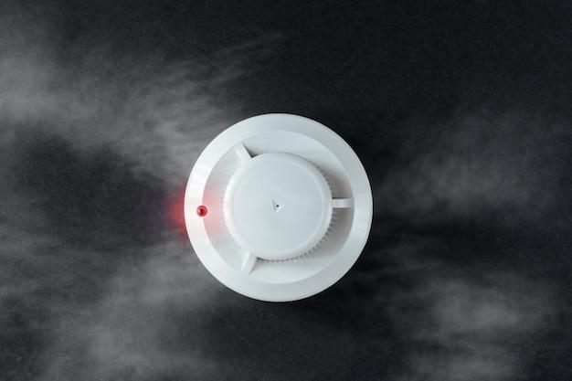 Detector de humo y detector de incendios sobre fondo negro.