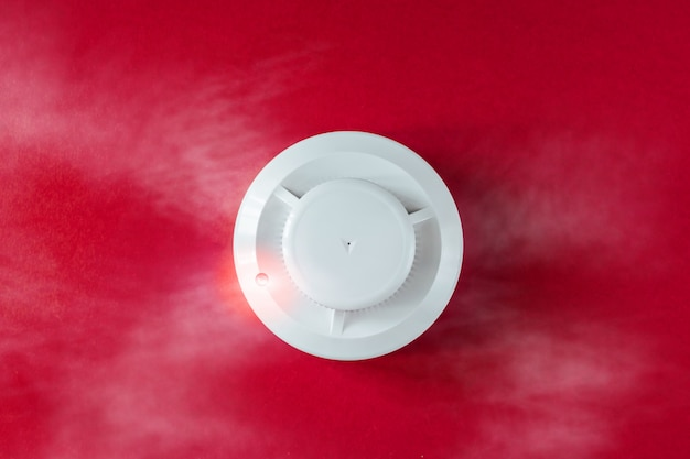 Detector de humo y detector de incendios sobre fondo rojo.