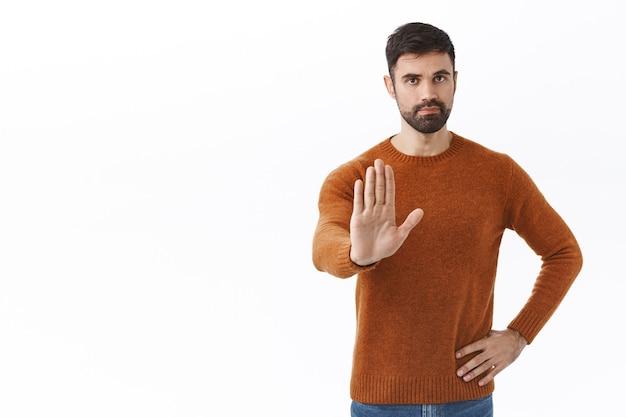Detén suficiente de esto. retrato de hombre guapo con barba y confianza, estirando la mano en señal de prohibición, desaprueba el comportamiento, prohíbe la acción, no salgas durante la cuarentena, pared blanca