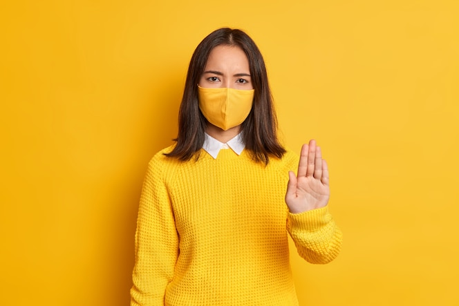 Detén el virus. grave mujer asiática enojada mantiene la palma hacia adelante en gesto de parada, usa máscara protectora como prevención del coronavirus