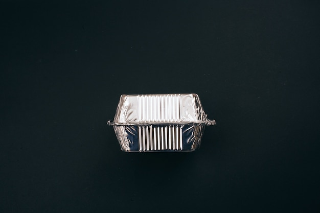 Detenga la contaminación plástica. recipiente de papel de aluminio plateado para alimentos sobre fondo oscuro, vista superior. no al plástico de un solo uso. un problema medioambiental, directiva de la ue