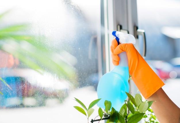 Detergente líquido en aerosol de mano de mujer en vidrio de ventana