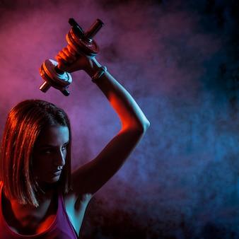 Determinado deportista con mancuernas en la oscuridad