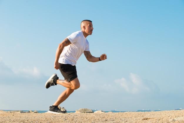 Determinado joven atleta corriendo en la playa