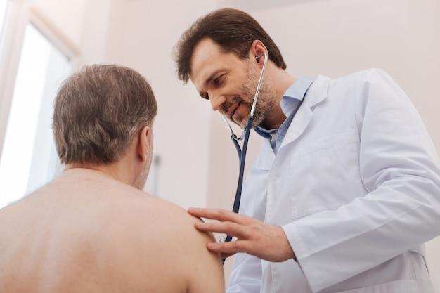 Determinado trabajador médico prominente encantador ejecutando una consulta aplicando un estetoscopio para diagnosticar a su paciente