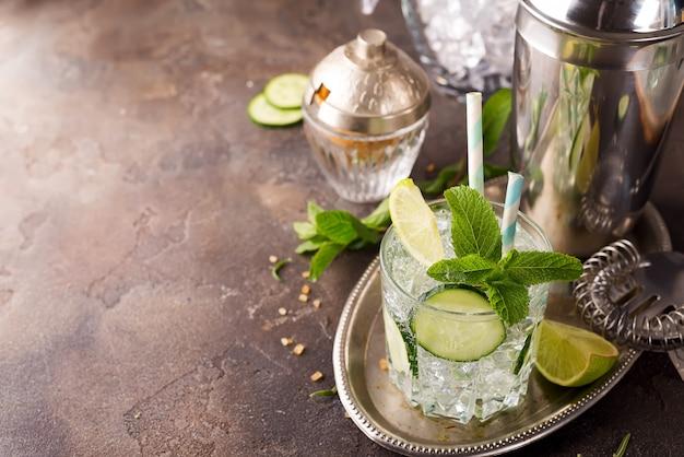 Detox infundido en agua de pepino. refrescante cóctel casero de verano sobre fondo de piedra.