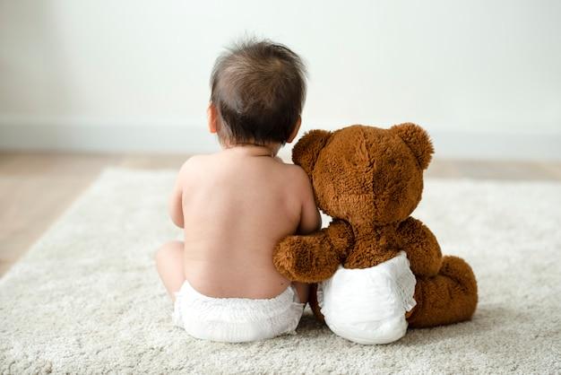 Detrás de un bebé con un osito de peluche.