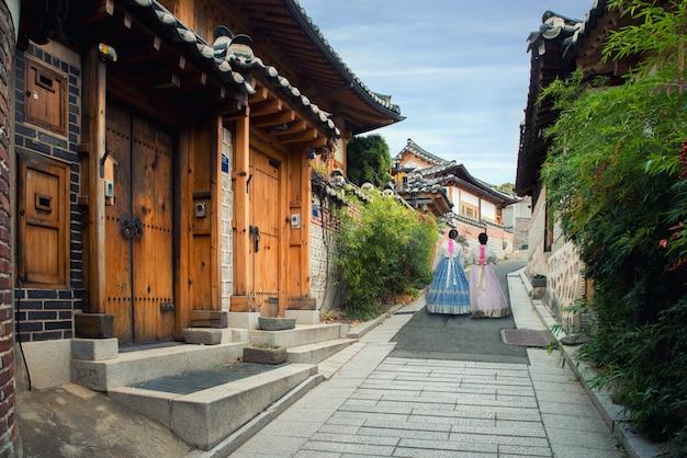 Detrás de dos mujeres que llevan hanbok caminando en el pueblo de bukchon hanok en seúl, corea del sur.
