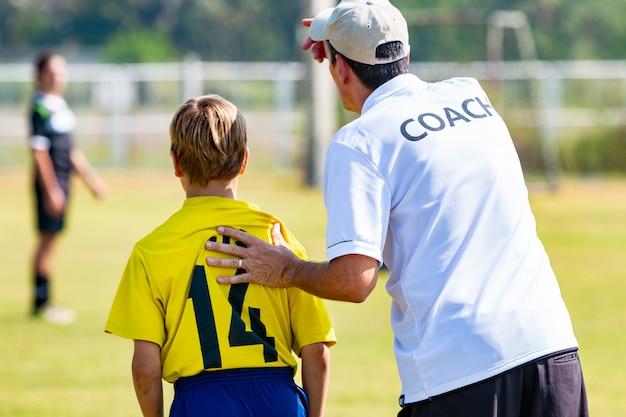 Detrás del entrenador de fútbol masculino a punto de enviar a su joven jugador en el juego