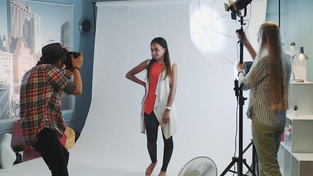 Detrás de escena en sesión de fotos: el fotógrafo le pide al asistente que dirija la iluminación a la modelo