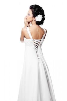 Detrás de la feliz feliz novia hermosa mujer morena en vestido de novia blanco con peinado y maquillaje brillante con flor en el pelo aislado en blanco