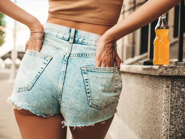 Detrás de la hermosa modelo sexy en ropa de pantalones cortos de jeans hipster de verano posando en la calle