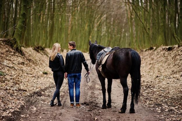 Detrás de la joven pareja elegante enamorada caminando con caballo en el bosque de otoño