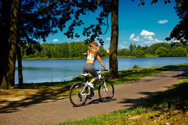 Detrás del modelo de mujer rubia sexy deporte caliente mujer montando en bicicleta en el parque verde de verano cerca del lago con el pelo elevado volando en el aire