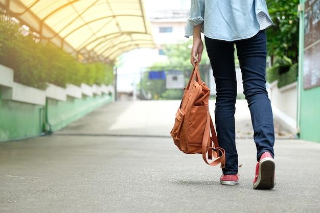 Detrás de la muchacha del estudiante que sostiene el bolso de escuela mientras que camina en el fondo del campus de la escuela, educati