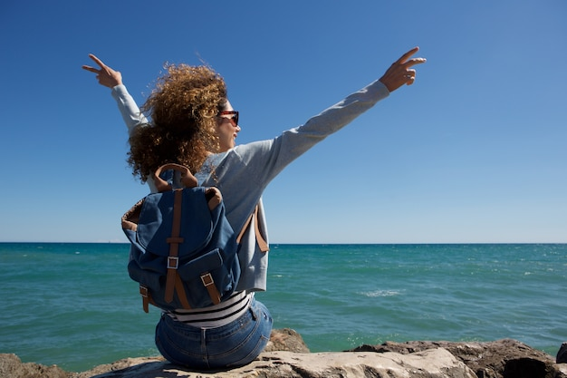 Detrás de una mujer joven disfrutando de la orilla del mar con los brazos levantados