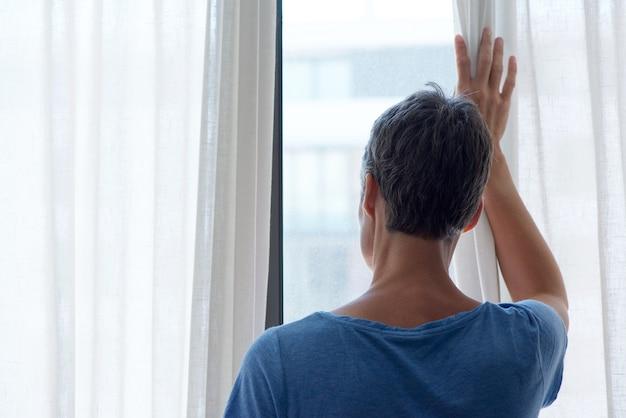 Detrás de la mujer de mediana edad mirando por la ventana