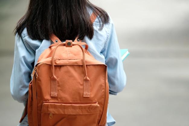 Detrás de la niña estudiante que sostiene libros y lleva la mochila mientras camina en el campus