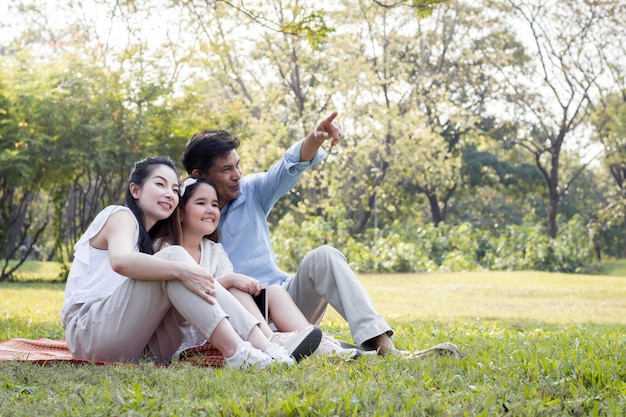 Detrás padres e hijos están jugando en el tapete del parque.