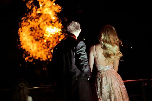 Detrás de la pareja enamorada que mira los fuegos artificiales