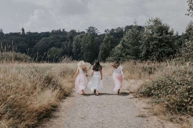 Detrás de tiro de chicas jóvenes con hermosos vestidos corriendo en el campo