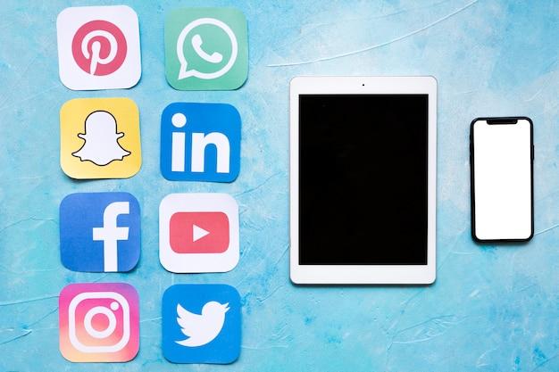 Dgital tableta y teléfono móvil cerca de pegatinas de iconos de redes sociales