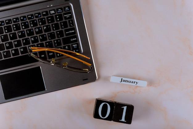 Día 01 de enero del mes, calendario en el lugar de trabajo de la oficina de negocios con espacio para laptop y gafas para texto