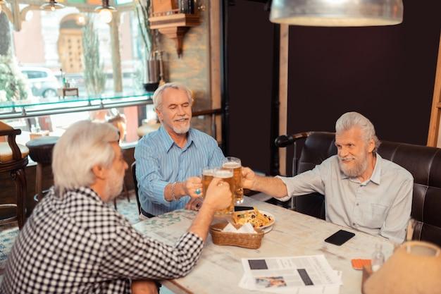 Día de la amistad. hombres jubilados celebrando el día de la amistad mientras beben cerveza en el pub