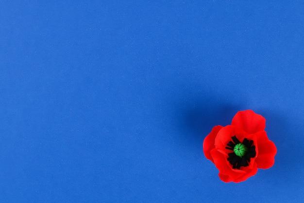 El día de anzac de la amapola roja de papel de diy, conmemoración, recuerda, papel de crepe del memorial day en fondo azul.