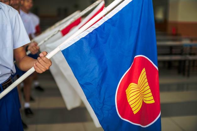 Día de la asean cae el 8 de agosto, mano sosteniendo banderas de tela de la asociación del sudeste asiático