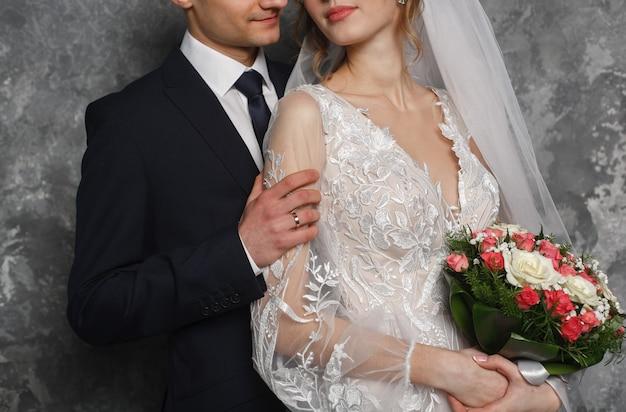 Día de la boda. recién casados besándose durante la ceremonia de matrimonio. abrazos apasionados de una pareja amorosa. novio con ojal abrazando suavemente a la novia con ramo de rosas. momento romántico de boda. recién casados