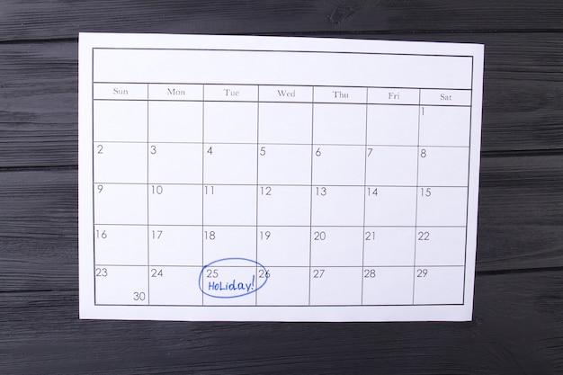 Día del calendario marcado como un día festivo por un marcador azul que planifica un día festivo en un calendario de papel de madera oscura ...