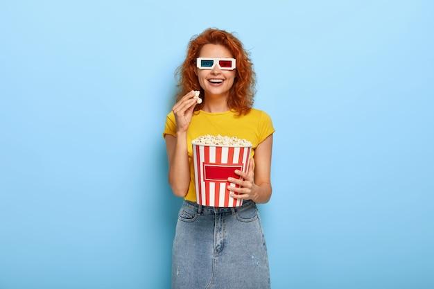 Día de cine y concepto de tiempo libre. joven optimista pelirroja feliz se divierte mientras ve una película interesante