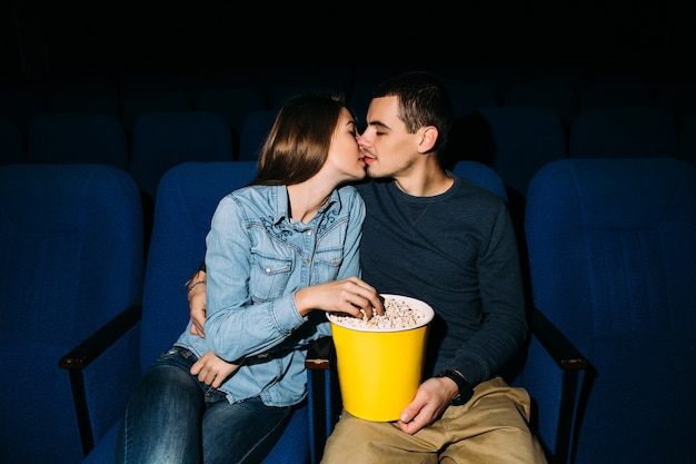 Día del cine joven hermosa pareja besándose mientras ve la película romántica en el cine.