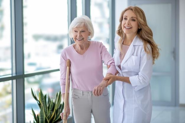 Día en clínica. doctor con una bata de laboratorio y un paciente caminando juntos y mirando positivo