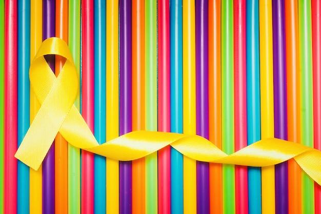 Día de concientización sobre el cáncer infantil. cinta amarilla sobre fondo de colores.