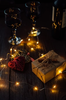 Día de san valentín. composición romántica de dos corazones, caja de regalo, luces y dos vasos de vino