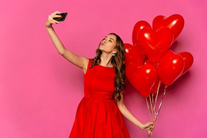 Día de san valentín. hermosa mujer tomando selfie, dando un beso