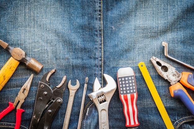 Día del trabajo, 1 de mayo. muchas herramientas útiles con espacio en blanco en la textura de fondo de los pantalones vaqueros.