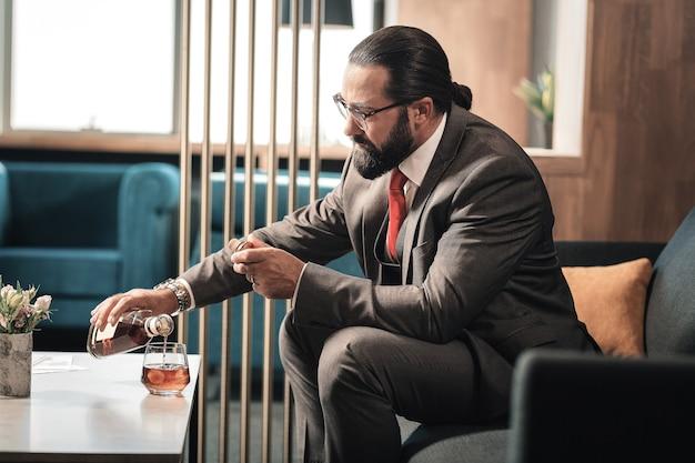 Día duro. hombre maduro con gafas y traje gris oscuro bebiendo coñac después de un duro día de trabajo