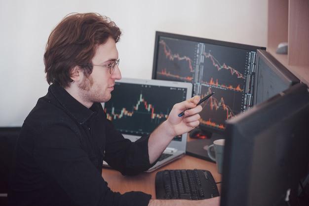 Día estresante en la oficina. hombre de negocios joven que lleva a cabo las manos en su cara mientras que se sienta en el escritorio en oficina creativa. concepto gráfico de la bolsa de comercio forex finanzas