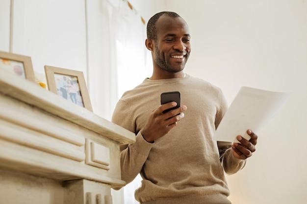 Día feliz. alegre hombre afroamericano barbudo riendo y sosteniendo su teléfono mientras está de pie cerca del estante con fotos y mirando la hoja de papel