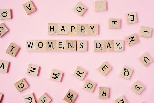 Día feliz de los woomans del mensaje de la visión superior deletreado en bloques de madera en fondo rosado
