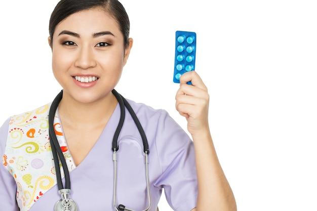 Uno por día. foto de estudio de una doctora sosteniendo medicación sonriendo alegremente aislado en blanco