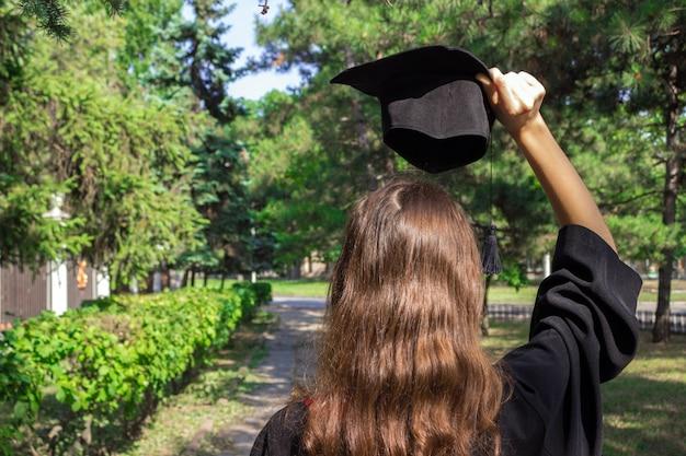 Día de la graduación, las imágenes de los graduados celebran la graduación con la mano puesta, un certificado y un sombrero en la mano.